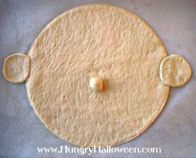 Roll out and cut a large circle out of your pizza crust then add two small circles of dough on either side for the vampire's ears and one round ball in the center for the nose.