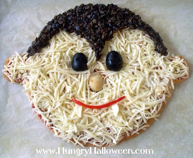Decorate the vampire shaped pizza with black olive eyes, chopped olive hair, a roasted red pepper smile, and garlic clove fangs.