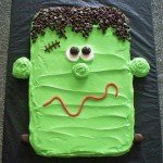 Frankenstein cookie cake decorated with green frosting, chocolate chips, marshmallows, and candy.