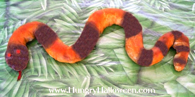 orange and black snack snack - hot dogs wrapped in pizza dough shaped like a snake