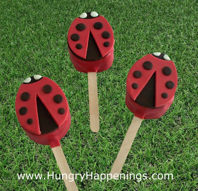Red chocolate dipped rice krispie treats decorated with red, black, and white modeling chocolate to look like ladybugs