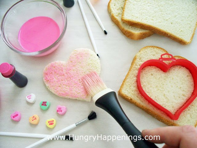 brush colored milk over heart-shaped bread to create conversation heart toast