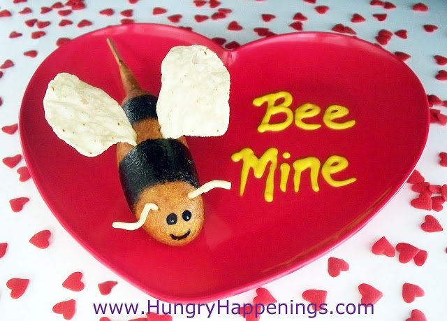 "bumble bee corn dogs with corn chip wings on a heart plate with ""bee mine"" written in yellow mustartd"
