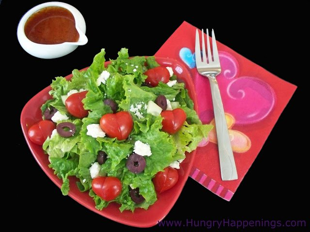 a Valentine's day salad topped with tomato hearts, cucumbers, feta cheese, and olives is served on a red plate with a serving of tomato vinaigrette