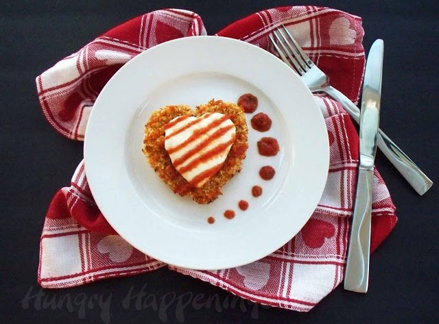 Panko bread crusted chicken breasts shaped like hearts topped with a heart-shaped mozzarella cheese drizzled with marinara sauce.