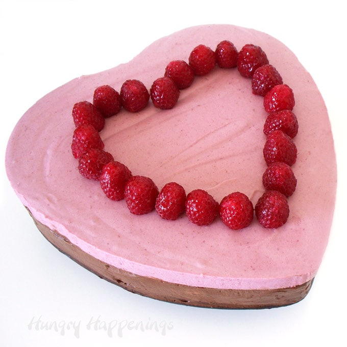 heart-shaped raspberry chocolate mousse cake topped with glazed raspberries