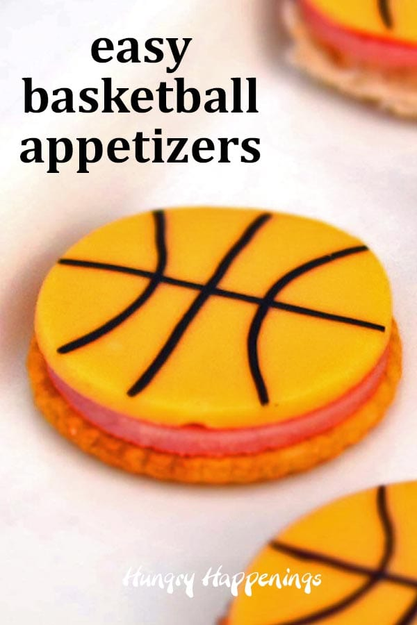 cracker topped with ham and a round slice of cheese decorated like a basketball