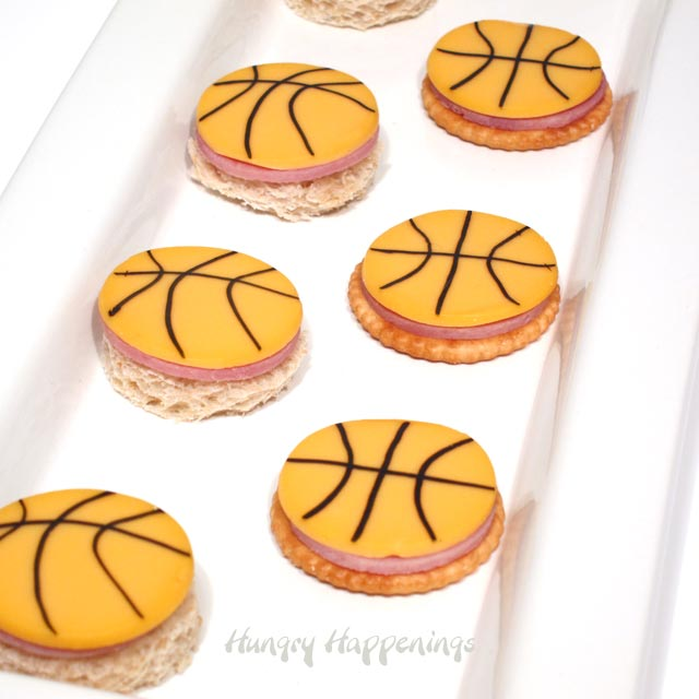 round crackers and bread topped with ham and basketball cheese slices