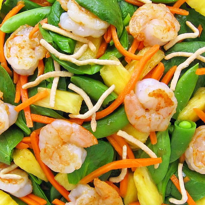 pan-seared shrimp and spinach salad tossed with carrots, sugar snap peas, pineapple, and ginger dressing