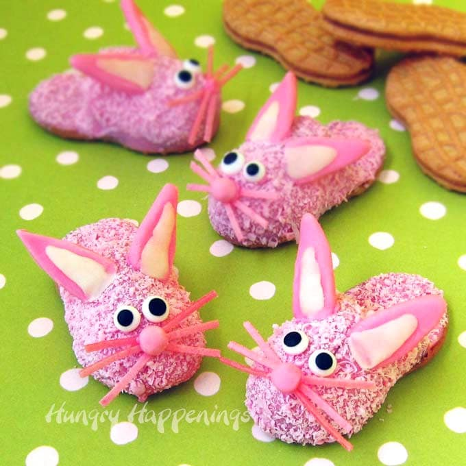 Pink Fuzzy Bunny Slipper Cookies with modeling chocolate ears, candy eyes, and edible pink grass whiskers