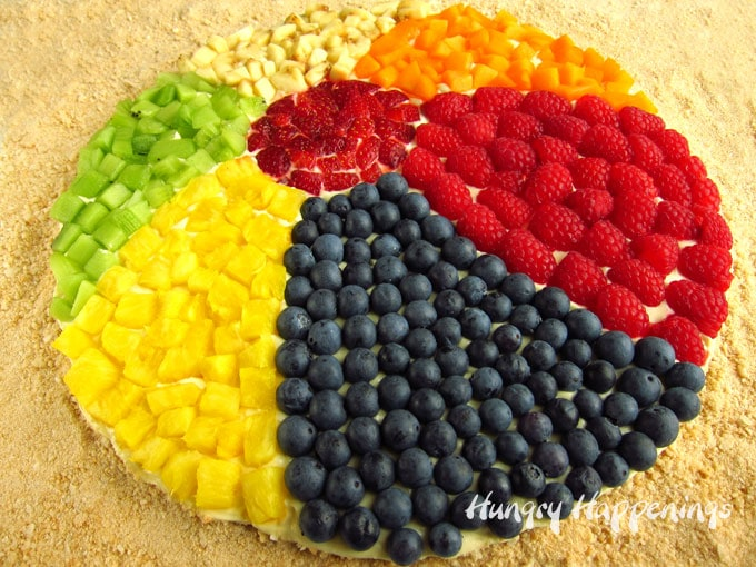 Beach ball fruit pizza topped with raspberries, strawberries, blueberries, pineapple, kiwi, bananas, and peaches.