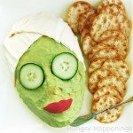 cheese ball shaped like a woman's face covered in a green guacamole mask, cucumber eyes, red pepper lips, and mozzarella head wrap