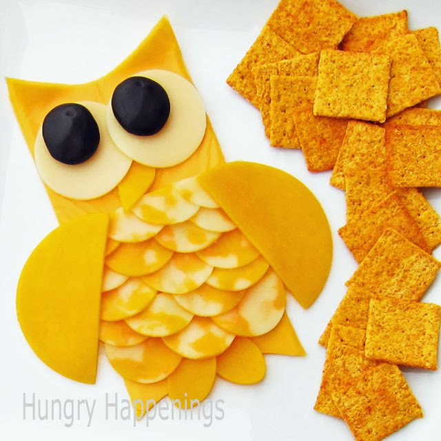 cheese slices assembled to look like an owl with black olive eyes served with crackers