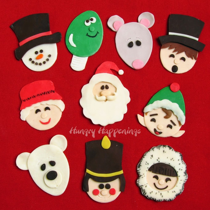 12 festive modeling chocolate Christmas toppers including a snowman, Christmas light, mouse, caroler, Mrs. Claus, Santa Claus, elf, polar bear, toy soldier, and a kid.