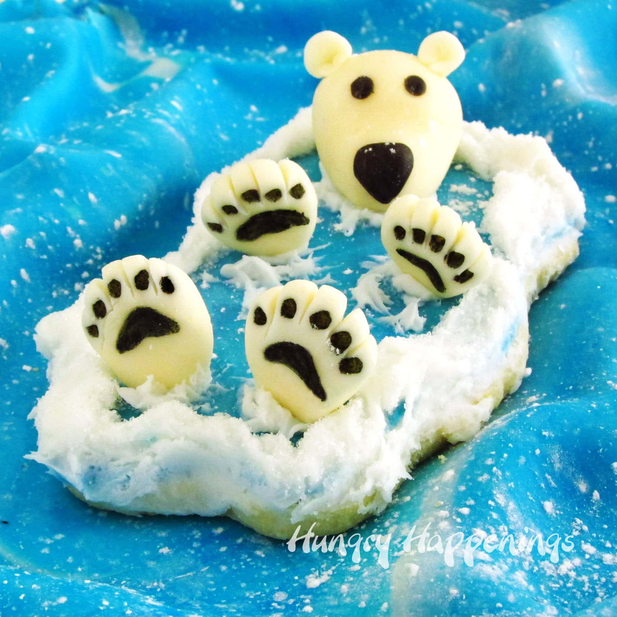 These polar bear cookies are so darn cute. Each has a 3 dimensional polar bear floating on it's back in a cookie ocean with it's big fluffy paws and head sticking up out of the modeling chocolate water.