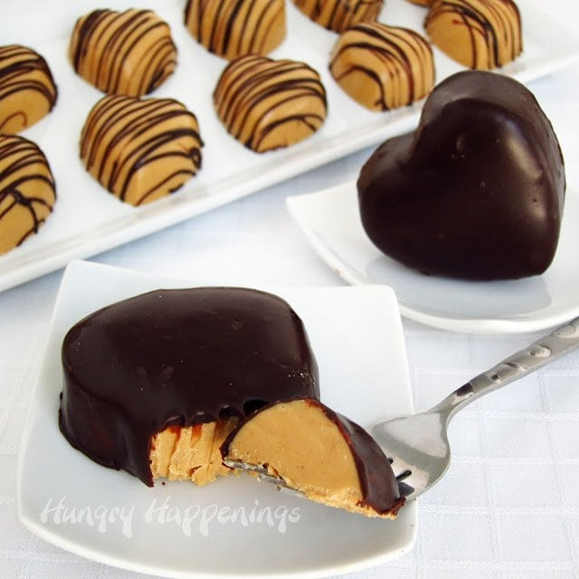 cut into a peanut butter fudge heart that's been coated in chocolate ganache