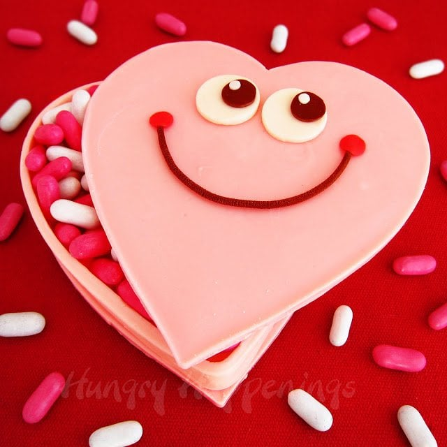 White chocolate heart-shaped box decorated with big eyes and a smile. Box filled with pink and white candies.