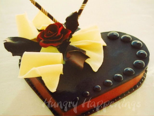 dark chocolate heart box decorated with a modeling chocolate rose, chocolate sticks, and chocolate ruffles