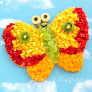 Butterfly fruit pizza topped with pineapple, grapes, strawberries,peaches, banana, and kiwi and decorated with chocolate chip eyes.