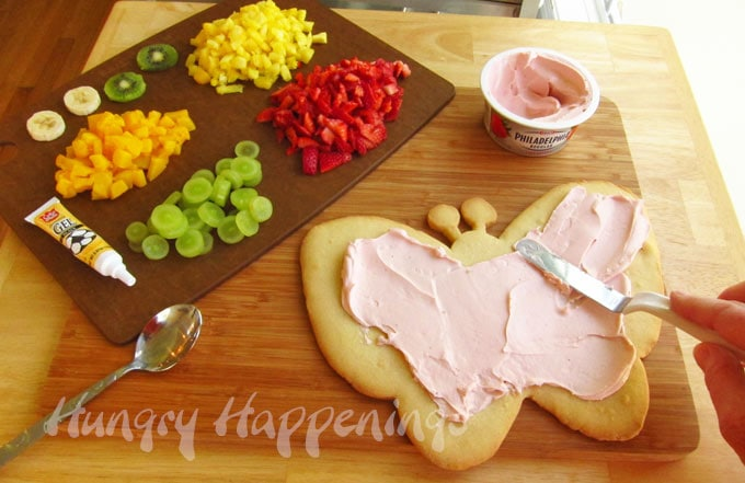 spread strawberry cream cheese over top of the butterfly cookie crust before topping it with fruit