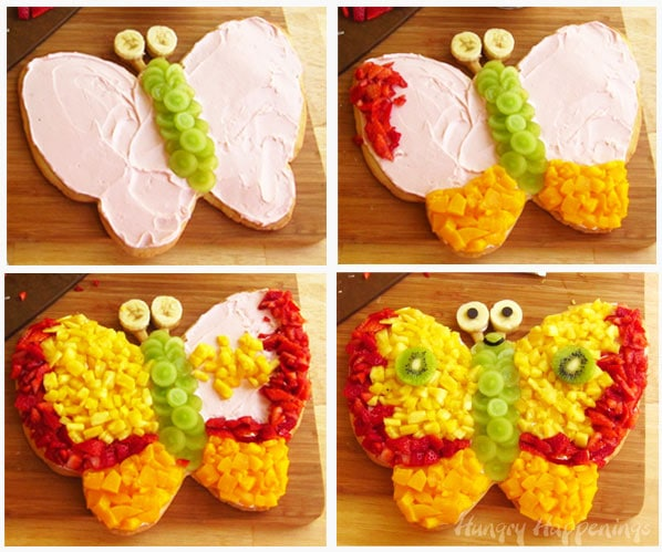 top the butterfly cookie with green grape slices for the body, peaches for the bottom of the wings, strawberries around the edge and pineapple to fill out the wings before adding banana slice eyes and kiwi slice spots