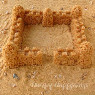 Caramel Rice Krispie Treat Sandcastle surrounded by cookie crumbs and seashells.