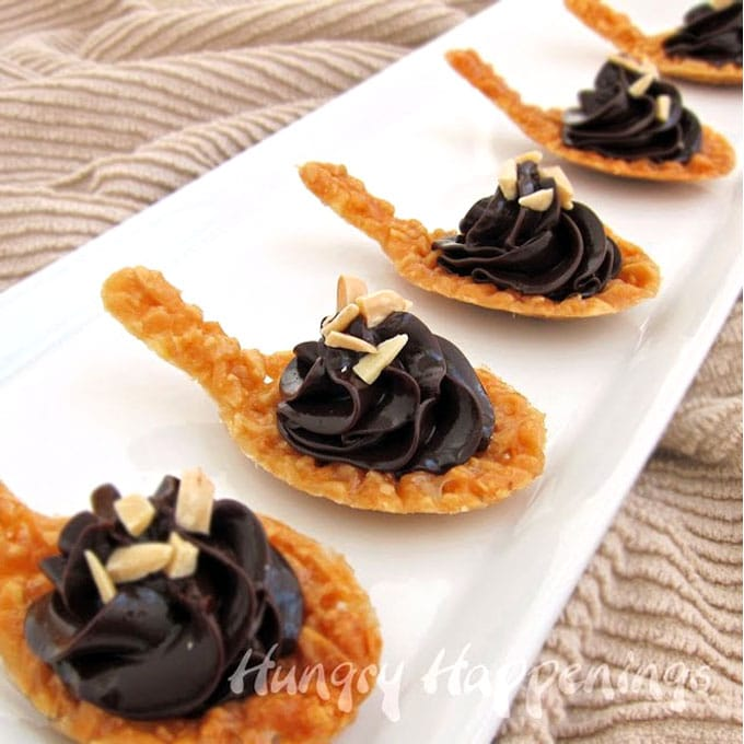 spoon-shaped almond nougatine cookies topped with chocolate ganache and slivered almonds