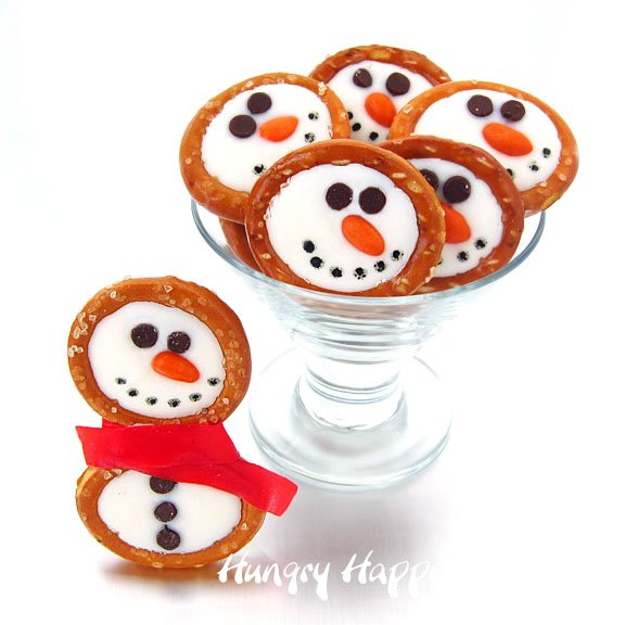 Decorate white chocolate pretzels with mini chocolate chips and candy coated sunflowers to make these cute winter themed treats. These Frosty Snowman Pretzels are as much fun to make as they are to eat and kids and adults will love them.