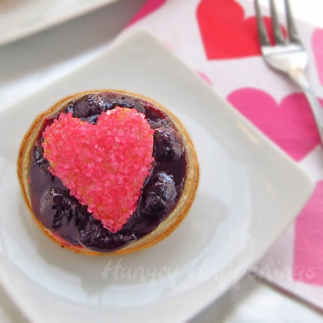 one mini blueberry pie topped with a heart-shaped pie crust that's covered in bright pink sugar