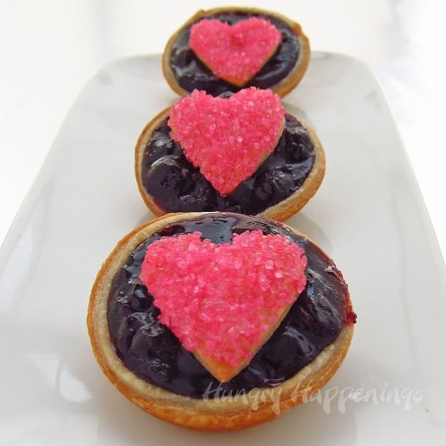 Bite-sized blueberry pies with heart-shaped pink sugar-coated pie crusts on top