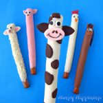 Chocolate-dipped pretzel farm animals including a sheep, pig, cow, chicken, and a horse.