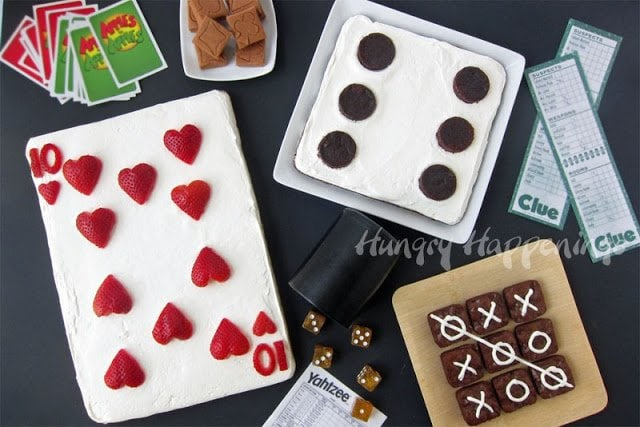 Fun family game night dessert ideas - strawberry fruit pizza playing card, brownie dice, and brownie tic tac toe game.