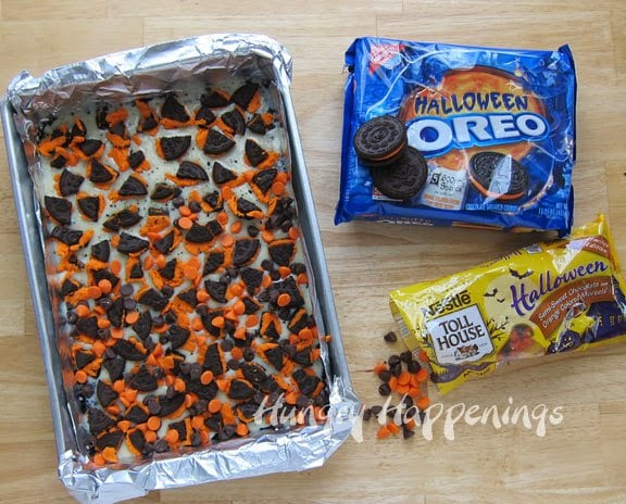 layer on pieces of Halloween OREO Cookies and orange and chocolate Nestle Halloween Morsels