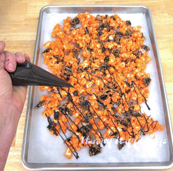 drizzle black candy melts over the orange-colored cookies and cream popcorn
