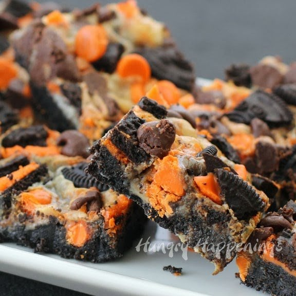 Cookies and Cream Magic Bars filled with orange and black OREO Cookies, semi-sweet, and orange-colored white chocolate chips