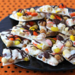 Candy Corn chocolate bark filled with peanuts, caramel, and Reese's Pieces.