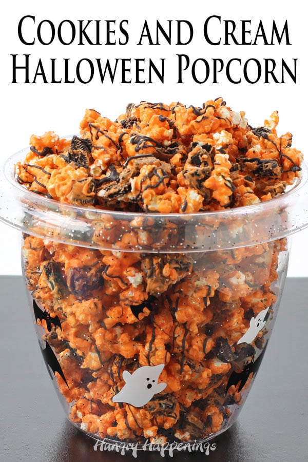 orange and black cookies and cream Halloween popcorn in a clear bowl printed with ghosts