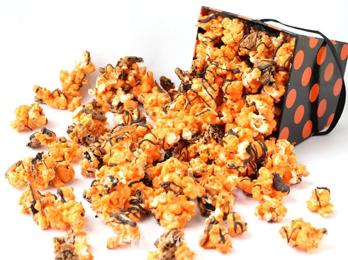orange and black cookies and cream Halloween popcorn spilling out of a orange and black polka dot box