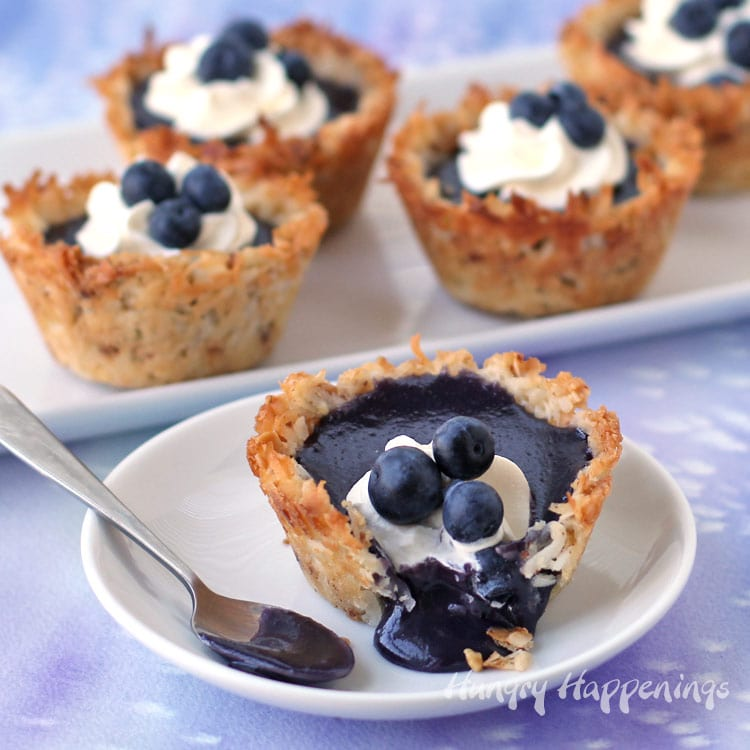 Coconut macaroon cookie cups filled with homemade blueberry curd topped with whipped cream and blueberries.