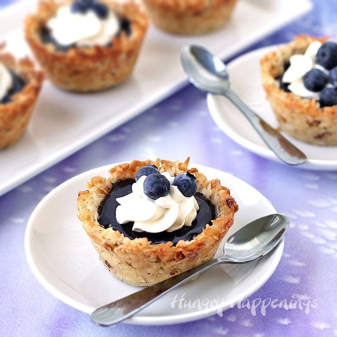 Soft and chewy Coconut Macaroon Cups filed with homemade blueberry curd are topped with a dollop of whipped cream and some fresh blueberries.