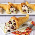 crescent-roll-cornucopia filled with cranberry turkey salad on a plate set next to a fork and Thanksgiving napkin