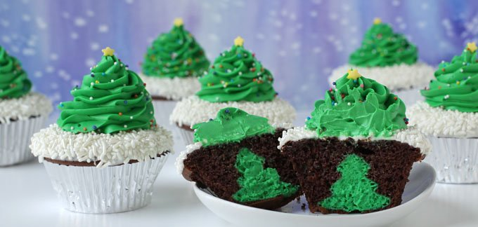 Christmas tree shaped cheesecakes are stuffed inside chocolate cupcakes.