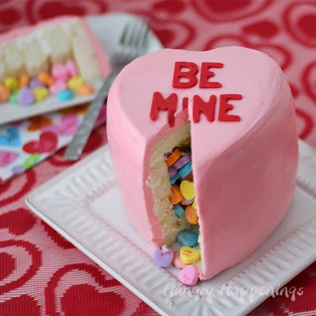 Pink conversation heart pinata cake filled with candy conversation hearts and decorated with pink frosting an red lettering.