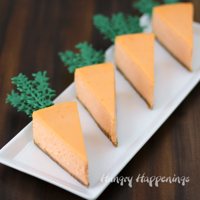 4 cheesecake carrots on a white plate set on a dark wood background