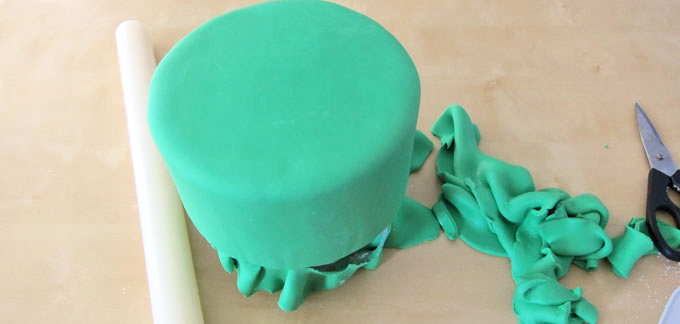 covering a round layer cake with green fondant