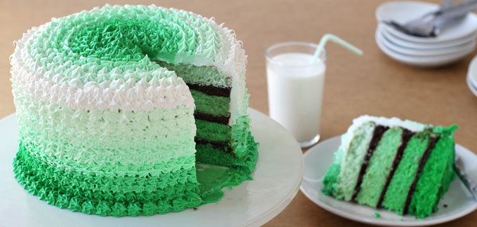 Layers of Creme de Menthe Cake and creamy chocolate ganache are covered in ombre stripes of green and white frosting.