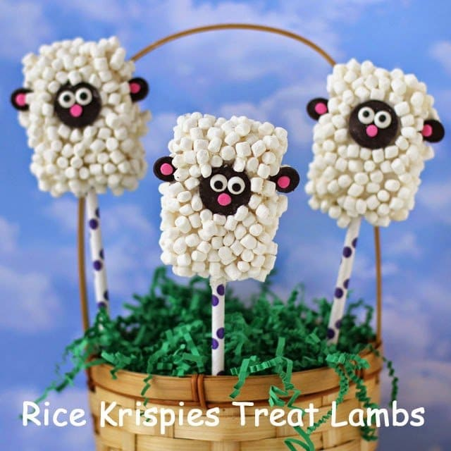 Rice Krispie Treat Lambs in an Easter basket with green paper shred in front of a cloudy blue background
