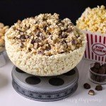 white chocolate popcorn bowl filled with white chocolate popcorn speckled with Twix candy bars