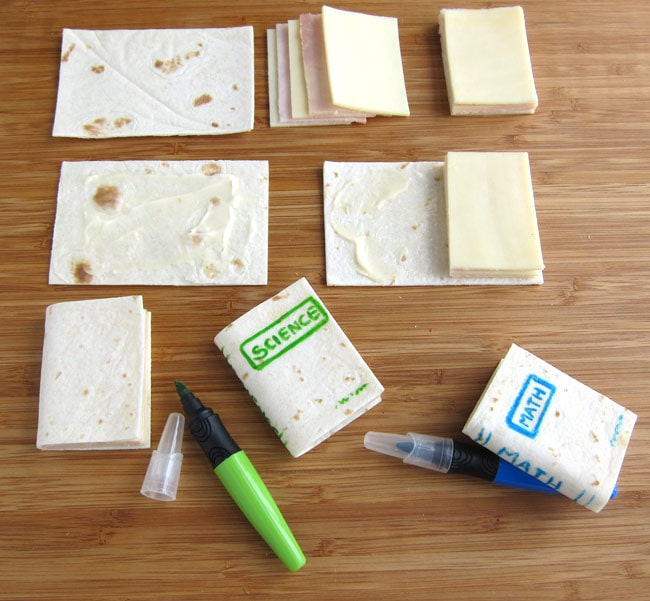 Spread mayonnaise over a tortilla rectangle. Then sandwich it around slices of cheese and ham before drawing the book's lettering one using food coloring markers.