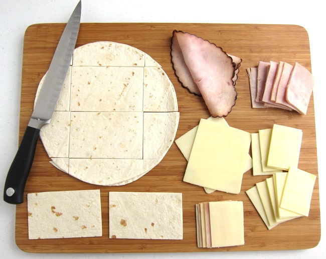 cut two rectangles out of a soft flour tortilla then cut lunch meat and cheese into small rectangles to create the pages of the school book sandwiches